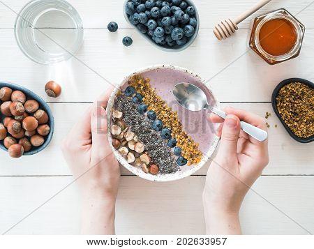 Eating healthy breakfast bowl. Buckwheat smoothie porrige, fresh berries, seeds and nuts, bee pollen in white ceramic bowl in woman hands on table. Clean eating, dieting, detox, vegetarian food concept