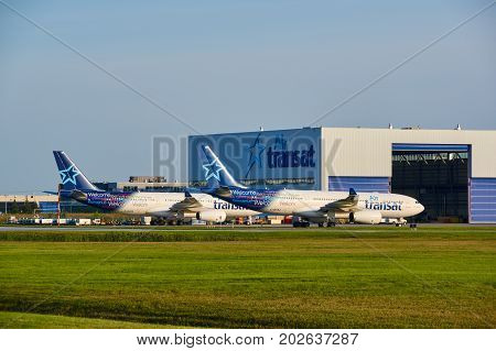 MONTREAL CANADA - AUGUST 28 2017 : Air Transat planes and garage. Air Transat is a Canadian leisure airline based in Montreal Quebec operating scheduled and charter flights serving 63 destinations