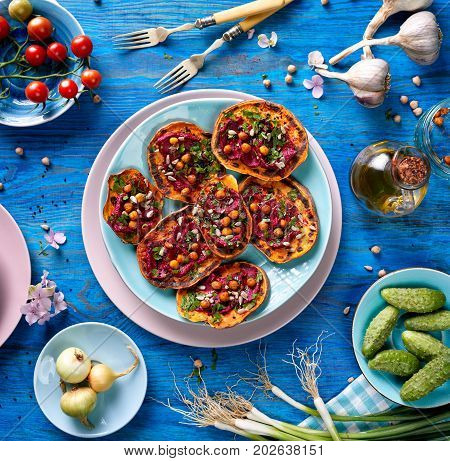 Sweet potato toast with beet hummus, grilled chickpeas, fresh parsley, nigella seeds  and sunflower seeds on a plate on a blue table, top view.  A nutritious and delicious vegan meal
