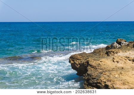 View on a turquoise Ocean in front of a clear Sky. Close-up of a Rock on front of a turquoise Sea. Beach and Nature Background.
