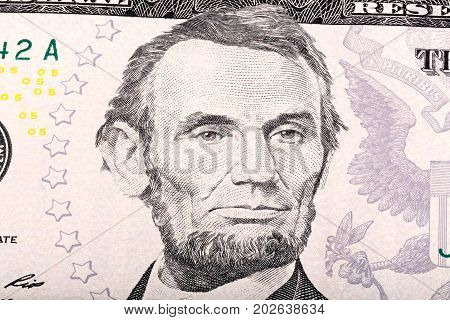 Stack of five U.S. Dollar. Close-up portrait of Abraham Lincoln. High resolution photo.