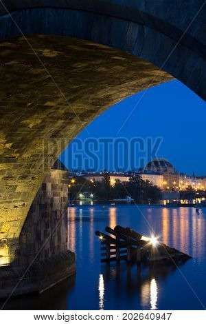 Second arch of the Charles bridge with Vltava river and bankside on the opposite side with the National Theater. Night picture of the embarkment and the National theater often called golden chapel