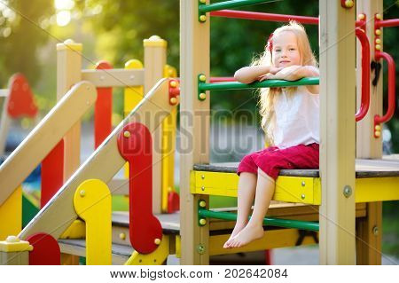 Cute Little Girl Having Fun On A Playground Outdoors In Summer.