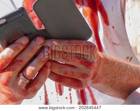 Fake blood wounded person using smartphone haloween