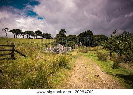 Pathway running past old ruined granite tin mine buildings set on Dartmoor. England UK