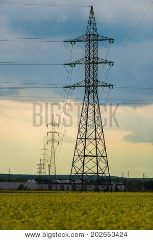 Electric pylons in beutiful rape field at the springtime