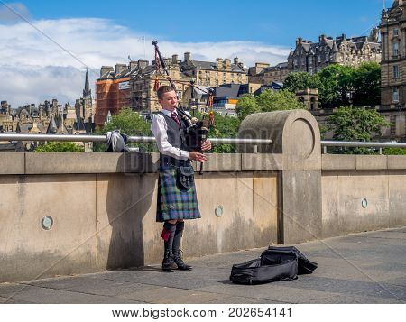 EDINBURGH, SCOTLAND - JULY 26: Unidentified Bagpiper playing music with bagpipes along the Mound on July 26, 2017 in Edinburgh Scotland. There are many bagpipers busking and entertaining tourists!