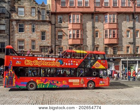 EDINBURGH, SCOTLAND - JULY 26: City sightseeing tour bus on the Royal Mile in the Old Town on July 26, 2017 in Edinburgh Scotland. Tout buses are a popular way to see Edinburgh.
