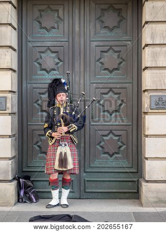 EDINBURGH SCOTLAND - JULY 26: A Scotsman wearing traditional Scottish outfit playing the bagpipes along the Royal Mile on July 26, 2017 in Edinburgh, Scotland. There are many pipers busking.