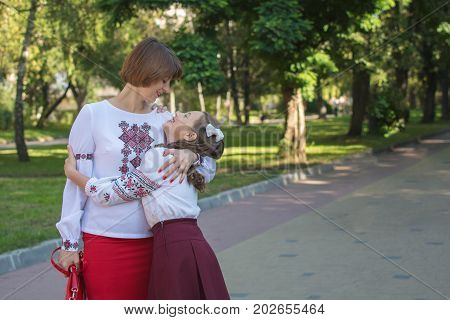 Daughter and mom stand and hug in embroidered shirts on the alley