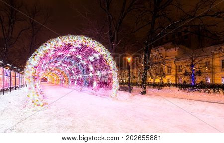 Entrance to the glowing decorative tunnel decorated with Christmas-tree toys and Christmas and New Year's attributes. City park at night in the center of Moscow