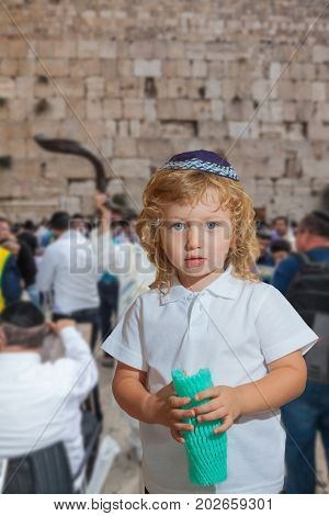 Shofar at the Wall of the Temple. Handsome little boy with blond side curls and blue eyes, in skullcap. Autumn Jewish holiday Sukkot. Jerusalem, Israel