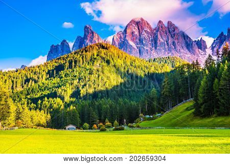 The sun illuminates grandiose gear rocks of Tirol. Small picturesque village in Alpine meadows. The Dolomites. The concept of eco-tourism