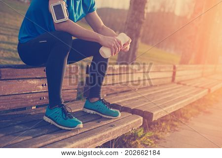 Tired Athlete Resting On The Bench In Park With Bottle Of Water (intentional Sun Glare And Vintage C