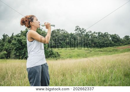 Asian women relax in the holiday. Drink Water on a green pasture.