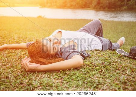 Asian women relax in the holiday. sleep relax on a green pasture.