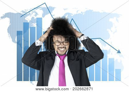 Image of Afro businessman looks stressful with a world map and declining arrow in the background