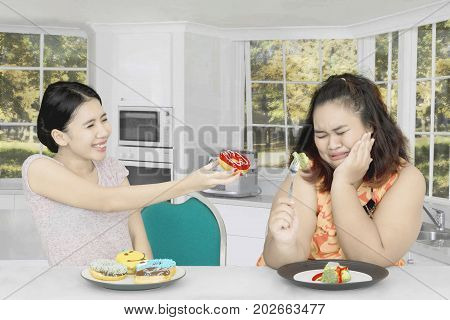 Picture of fat woman eating salad and refuse to eat donuts from her friend while sitting at home