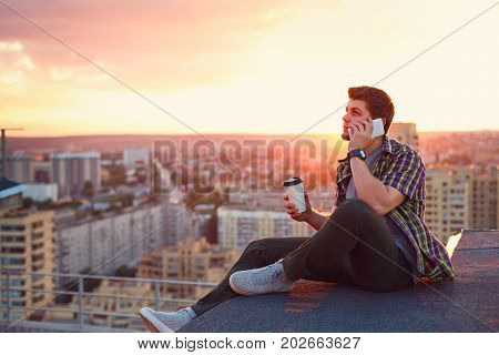 A hipster man drinks coffee and talks on his cell phone. He sits on the roof of a high-rise building at sunset