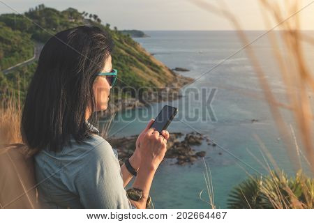 Young traveler woman use mobile phone taking of photo at beautiful of nature at top of mountain and sea viewtravel wanderlust backpacker concept.