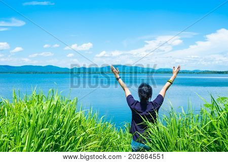 Happy young traveler woman raised arm up to sky enjoying a beautiful of nature at top of mountain and sea viewFreedom wanderlust backpacker concept.