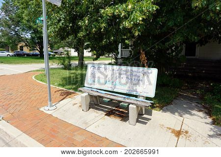JOLIET, ILLINOIS / UNITED STATES - JULY 20, 2017: An advertisement on a rotted bench, at a bus stop on Plainfield Road, provides the phone number of the Sexual Assault Service Center.