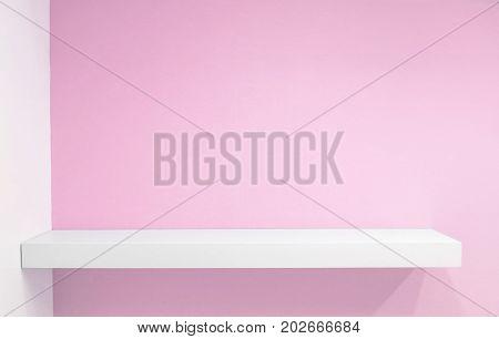 Empty white shop shelf retail shelf on pink vintage background.