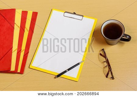Clipboard with white sheet folders cup of tea glasses and pen on desk