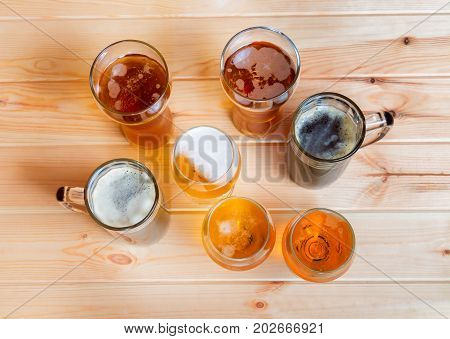 Beer glasses and beer mugs on wooden table. Top view.