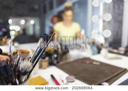 Professional make-up, brushes and accessories on the table.Equipment of facial make over art. Tools of professional visage studio. Make up artist at work reflecting in the mirror. Defocused.