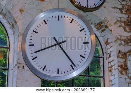 Large clock in front of the window in an industrial factory on a brick wall.