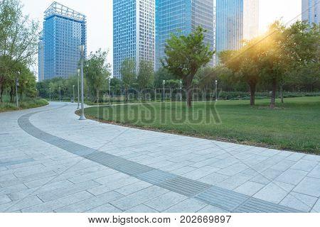 park pedestrian walkway and modern skyscrapers,dalian city,china.