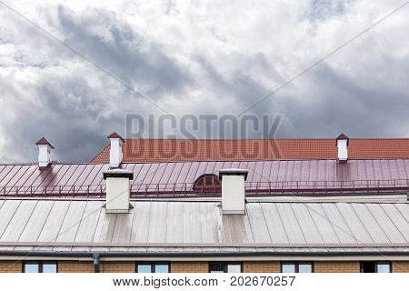 Tiled Roofs Of Old Buildings With Chimneys In Rainy Day