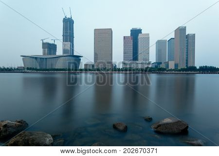 Dalian city waterfront downtown skyline with rock beach on foreground,China.