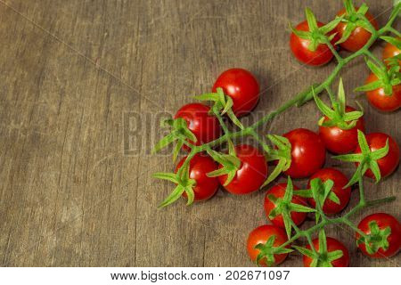 Fresh cherry tomato on rustic wood table. Top view cherry tomato for background or wallpaper. Prepare fresh cherry tomato for home cooking look so delicious. Top view with copy space in vintage tone. Tomato in vegetable background concept.