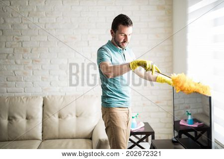 Handsome Latin Man Dusting His House
