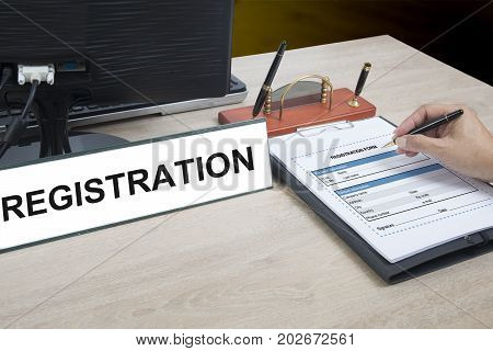 Someone writing personal information into registration form.
