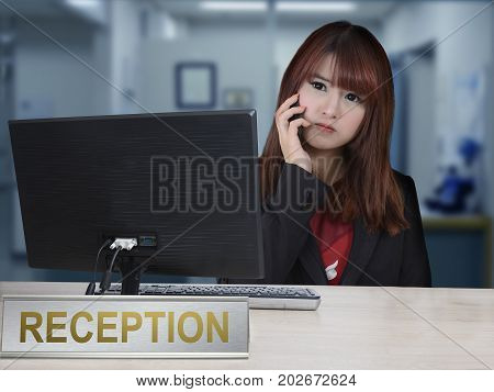 Working girl receive telephone call while sitting behind frontdesk.