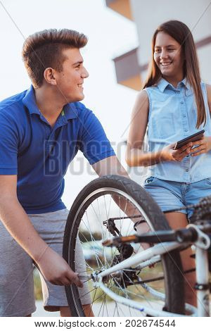 Teenager boy repair tire on bicycle female friend standing next to him using digital tablet for instructions summer outdoor photo