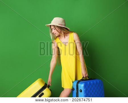 Young woman with suitcases on color background. Luggage overweight concept