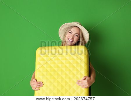 Young woman with suitcase on color background. Luggage overweight concept