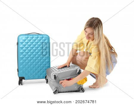 Young woman trying to pack her luggage on white background. Luggage overweight concept