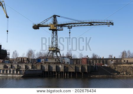Stationary industrial crane river shipyard on the background of blue sky
