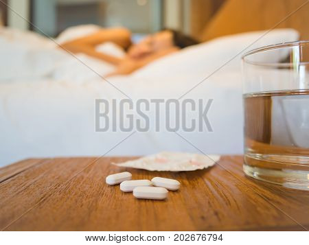 Sick woman covered with a blanket lying in bed with high fever and a flu focus on the medicine. Healthcare medical supplements concept.