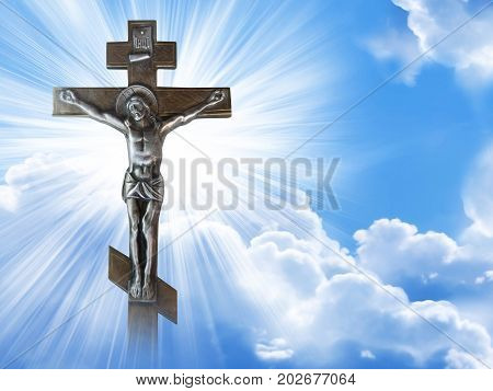 Silhouette of the crucified Jesus Christ on the cross against the blue sky. The Biblical prophet is a symbol of death. Calvary Christmas Easter background.