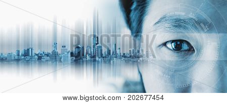Close-up Asian businessman's eye , with futuristic technology visual effect and city hologram