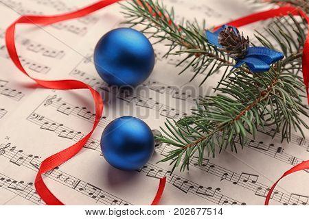 Blue balls on music sheet. Christmas songs concept