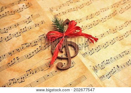 Wooden treble clef on music sheets. Christmas songs concept