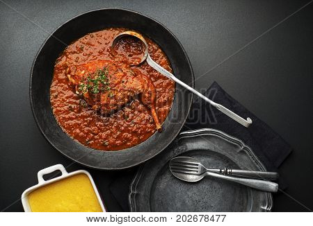 Meat stew with vegetable and tomato sauce on black background