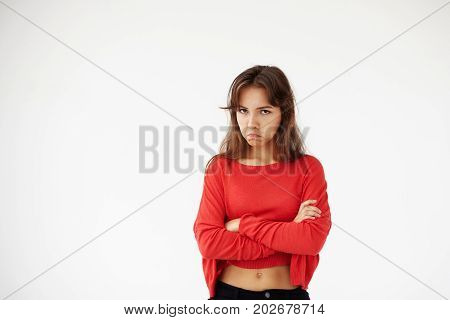 Studio shot of casually dressed young Hispanic female with dark hair pouting keeping arms folded looking at camera with unhappy and offended grimace. Negative human expressions and emotions